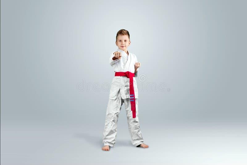 Fondo creativo, bambino in kimono bianco su un fondo leggero Il concetto delle arti marziali, karat?, sport da allora immagine stock