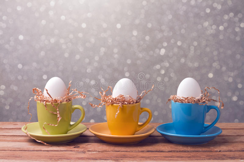Fondo creativo del día de fiesta de Pascua con los huevos en tazas de café imagen de archivo libre de regalías