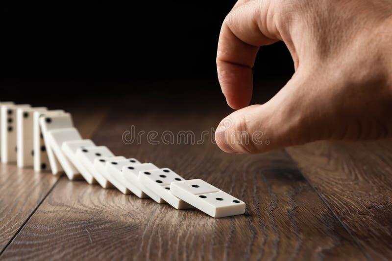 Fondo creativo, domin?s blancos que empujan manualmente masculinos, en un fondo de madera marr?n Concepto de efecto de domin?, ca imagen de archivo