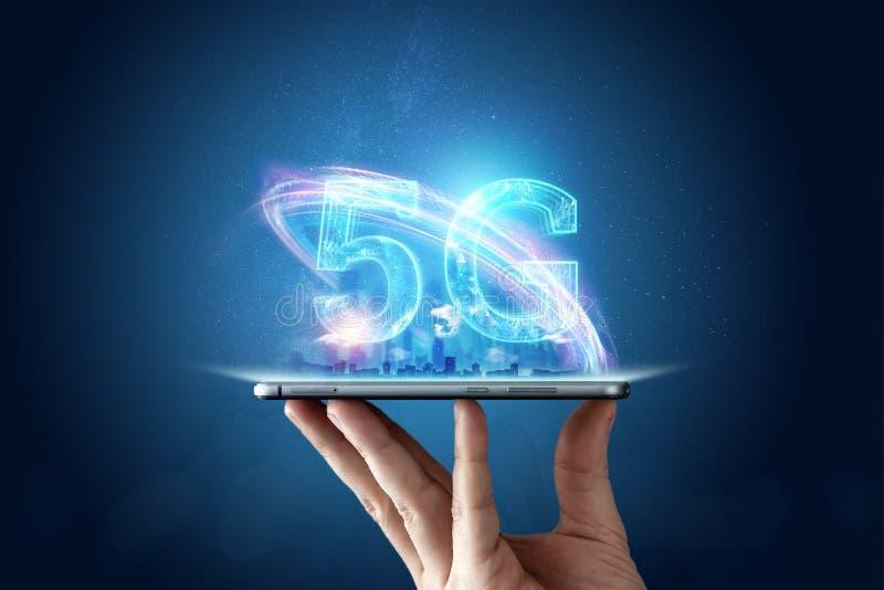 Fondo creativo, mano masculina que sostiene un teléfono con un holograma 5G en el fondo de la ciudad fotografía de archivo