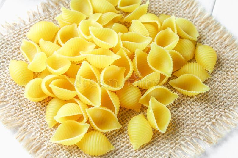 Fondo culinario con la pasta del conchiglie sulla tavola di legno Pasta sotto forma di conchiglie su un sacco con prezzemolo immagini stock
