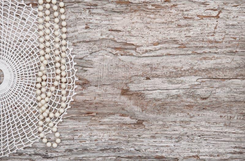 Fondo d'annata con la collana della perla e pizzo sul vecchio legno fotografia stock