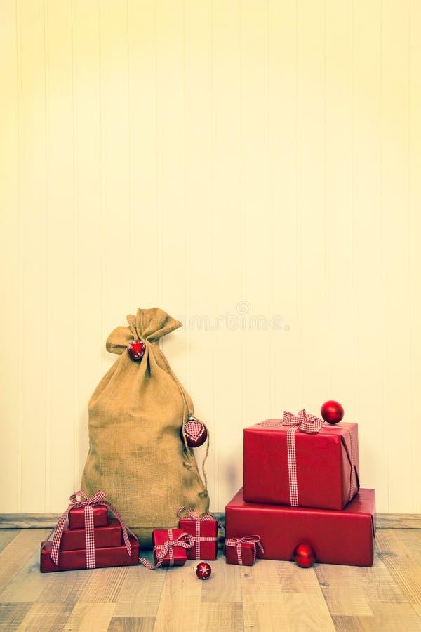 Fondo d'annata di natale con il sacco di Santa e del regalo rosso fotografia stock