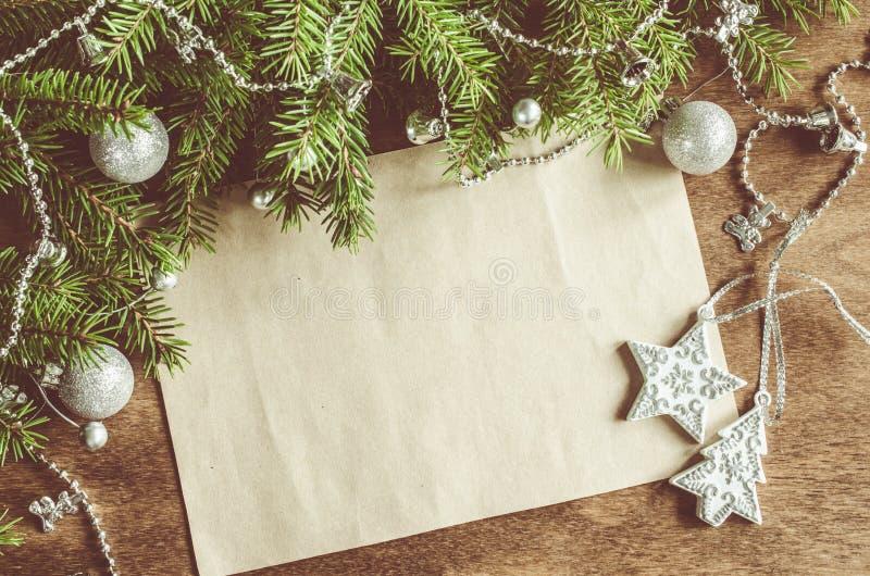 Fondo d'annata di Natale con la decorazione di natale Cartolina in bianco sul bordo di legno Fuoco selettivo, spazio per testo immagine stock