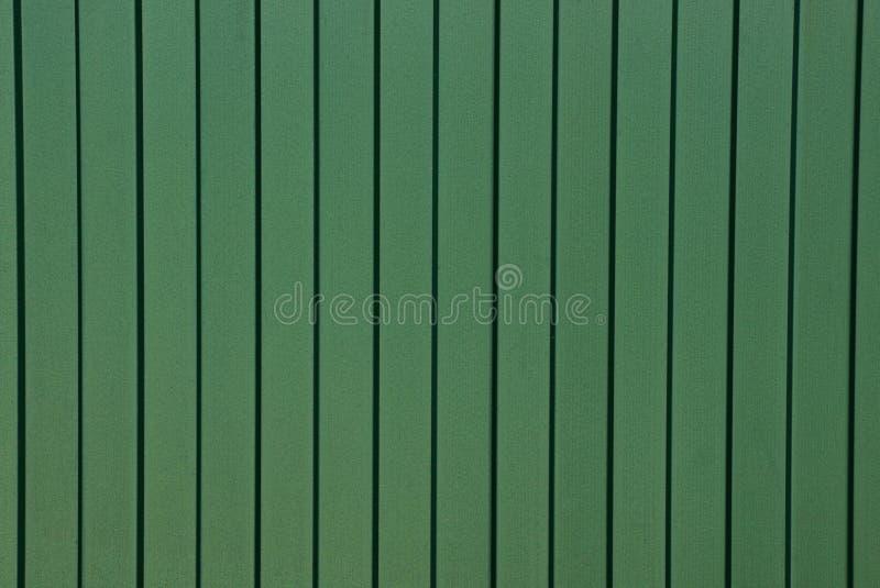 Fondo da un frammento di una parete verde del metallo di un recinto fotografie stock