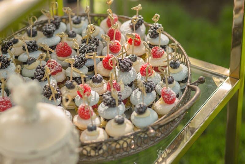 Fondo da un grande bello piatto dei dessert francesi tradizionali del maccherone con le bacche ed i frutti, riempito  immagine stock libera da diritti