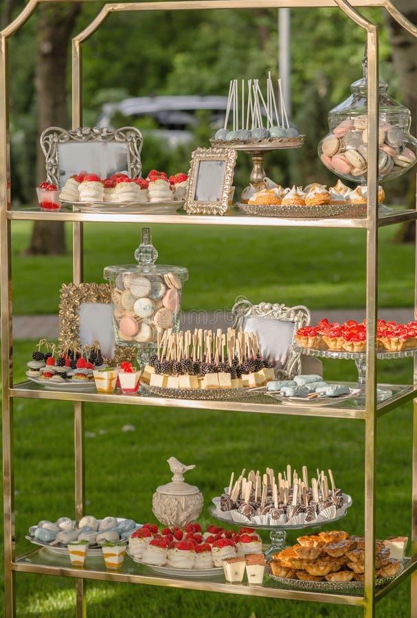 Fondo dai dessert assortiti per gli ospiti di una festa nuziale o di una festa di compleanno dai dadi del cioccolato della frutta fotografia stock libera da diritti