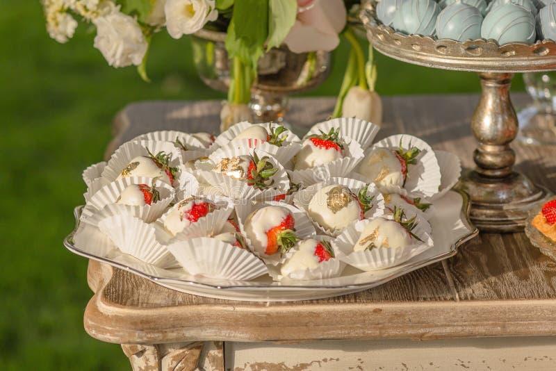 Fondo dai dessert assortiti per gli ospiti di una festa nuziale o di una fragola di compleanno in cioccolato al latte bianco fotografia stock libera da diritti