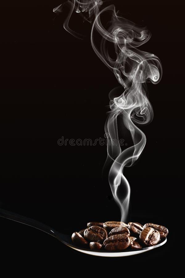 Fondo de bebida de las judías de café tostadas en cuchara aisladas sobre fondo oscuro con humo aromático fotos de archivo libres de regalías