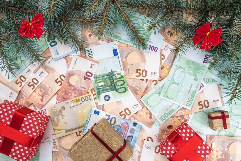 Fondo de billetes de banco de diverso valor Muchos regalos, ramas del abeto, atmósfera de la Navidad imagen de archivo libre de regalías
