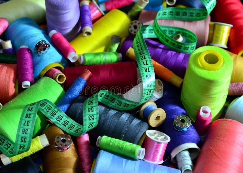 Fondo de bobinas con los hilos multicolores para coser Costura, cosiendo y adaptando concepto foto de archivo libre de regalías