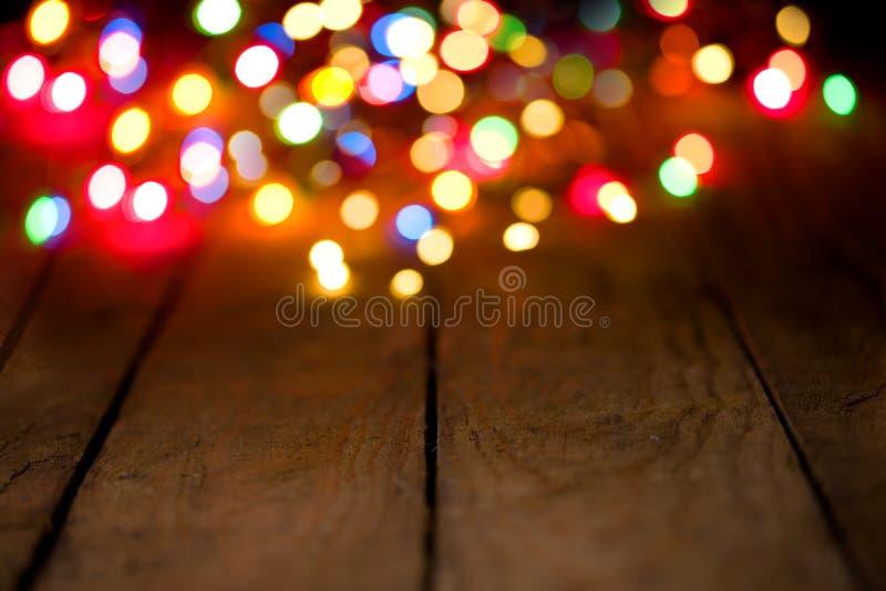 Fondo de Bokeh con las luces coloridas en los tableros de madera fotografía de archivo