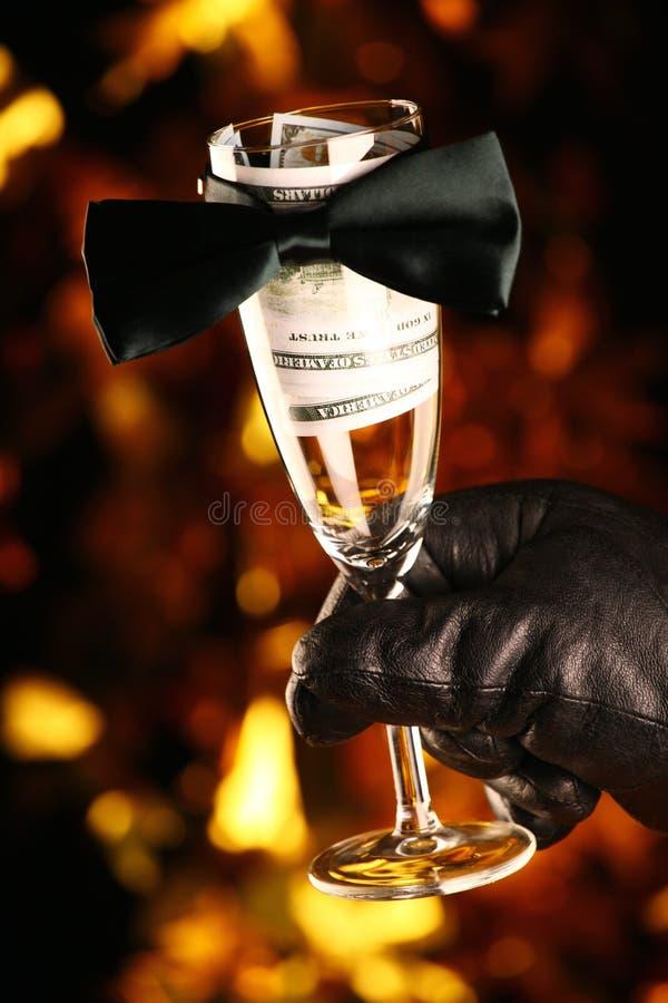 Fondo de cristal del oro del dólar del dinero de la corbata de lazo del champán negro de los guantes de cuero fotografía de archivo