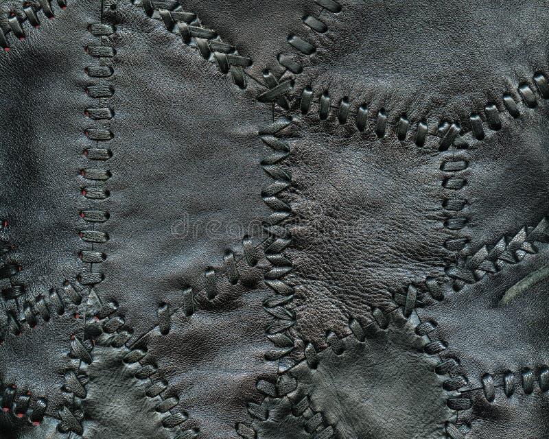 Fondo de cuero negro cosido de pequeños pedazos de cuero con el hilo de cuero fotos de archivo