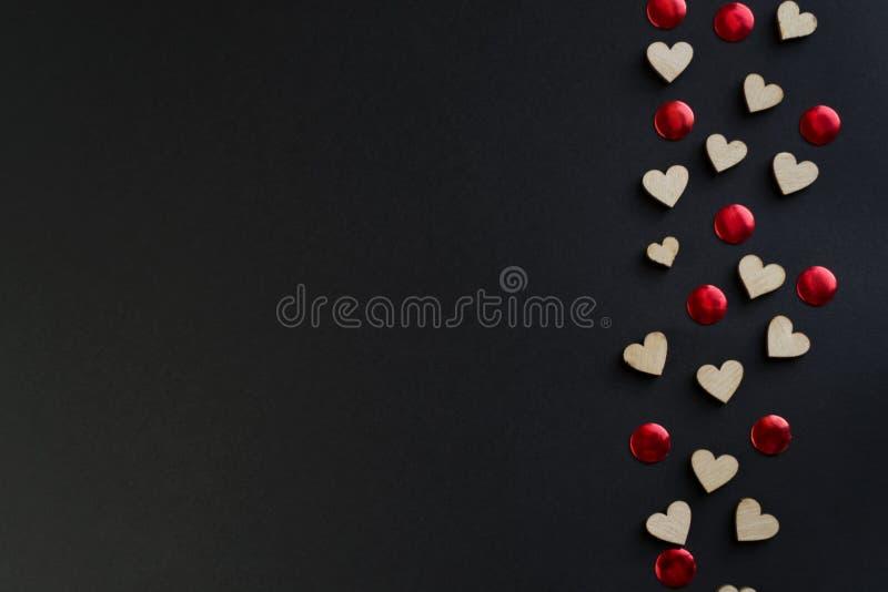 Fondo de día de San Valentín con los corazones rojos en la tabla negra, visión superior foto de archivo