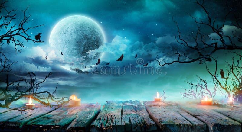 Fondo de Halloween - tabla vieja con las velas y las ramas en la noche fantasmagórica fotos de archivo libres de regalías