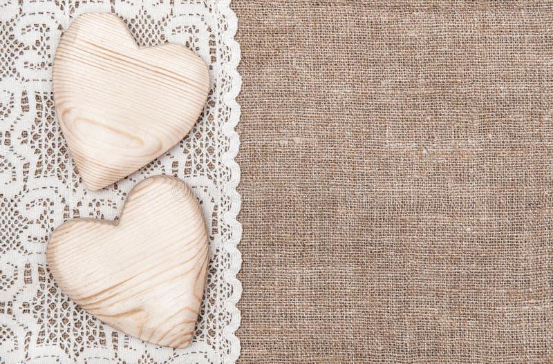 Fondo de la arpillera con el paño de encaje y los corazones de madera fotos de archivo