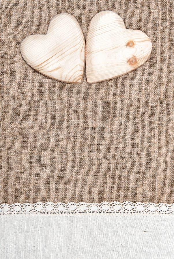 Fondo de la arpillera con el paño de encaje y los corazones de madera foto de archivo libre de regalías