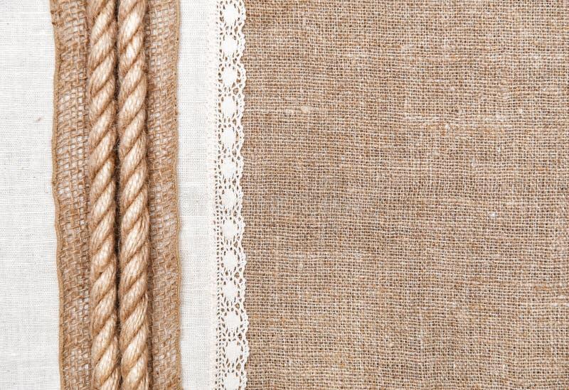 Fondo de la arpillera con el paño de lino y la cuerda imágenes de archivo libres de regalías