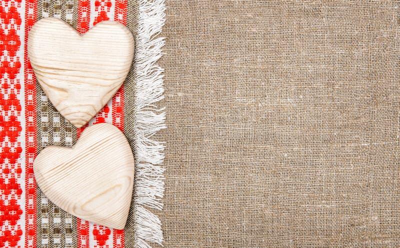 Fondo de la arpillera confinado por el paño del país y los corazones de madera imagen de archivo libre de regalías