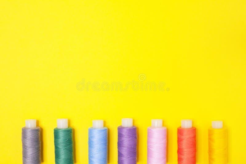 Fondo de la artesanía Fije de carretes multicolores del hilo en fondo amarillo con el espacio de la copia Accesorios para la cost foto de archivo libre de regalías