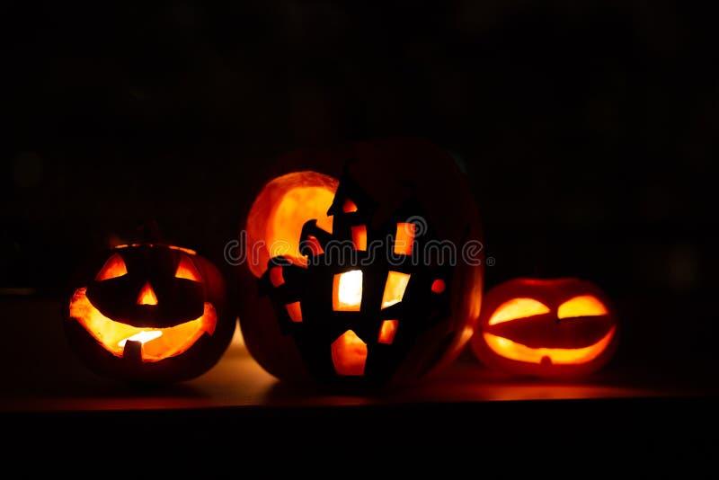Fondo de la calabaza de Halloween, tres calabazas con el fondo negro oscuro Dos calabazas y casas hechas frente asustadizas forma foto de archivo libre de regalías