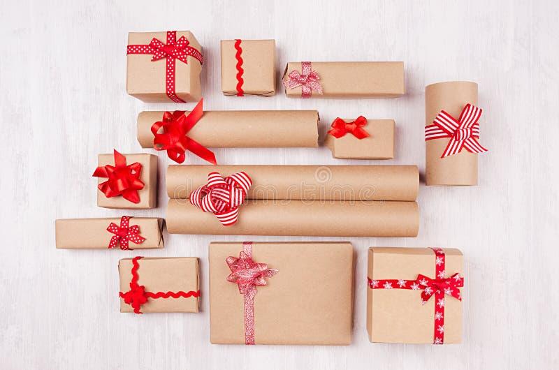 Fondo de la celebración del Año Nuevo - regalos de papel del arte del diferente tipo con las cintas y los arcos rojos en el tabló imagen de archivo