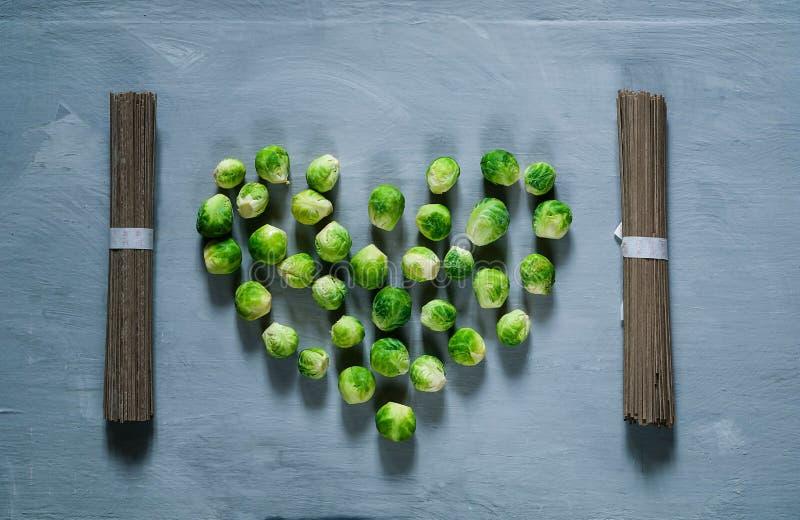Fondo de la comida de la col del briussel en la forma del corazón y de los tallarines japoneses, visión superior, espacio de la c imagen de archivo