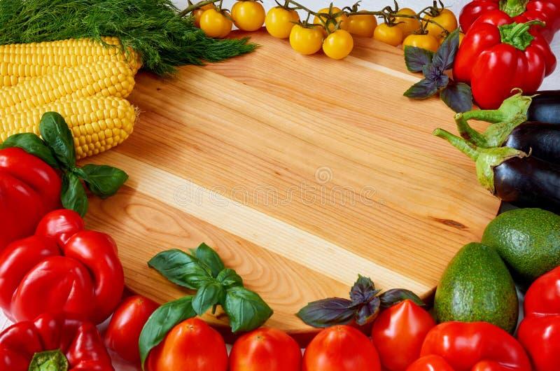 Fondo de la comida con el espacio de la copia para el texto Verduras e hierbas orgánicas frescas en la tabla de madera: paprika,  fotografía de archivo