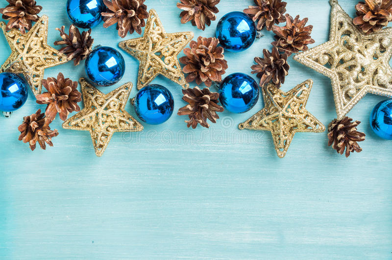 Fondo de la decoración de la Navidad o del Año Nuevo: conos del pino, bolas de cristal azules, estrellas de oro en el contexto pi imagen de archivo
