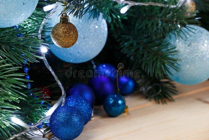 Fondo de la decoraci?n de la Navidad o del A?o Nuevo: ramas del piel-?rbol, bolas de cristal coloridas en fondo de madera imágenes de archivo libres de regalías