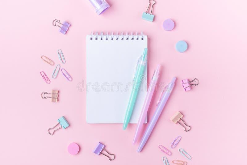 Fondo de la escuela con los cuadernos y los accesorios coloridos en colores pastel del estudio en fondo rosado de nuevo a concept fotografía de archivo libre de regalías