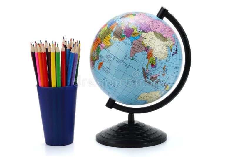 Fondo de la escuela Globo con los lápices coloreados aislados en el fondo blanco imágenes de archivo libres de regalías