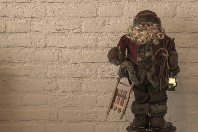 Fondo de la Feliz Navidad, una decoración de la muñeca de Papá Noel que sostiene un trineo y una linterna encendida que está ilum imagenes de archivo