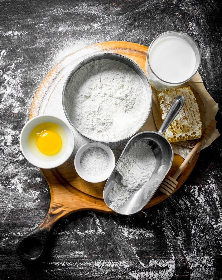 Fondo de la hornada Harina con la miel, la leche y el huevo en la tabla de cortar imágenes de archivo libres de regalías