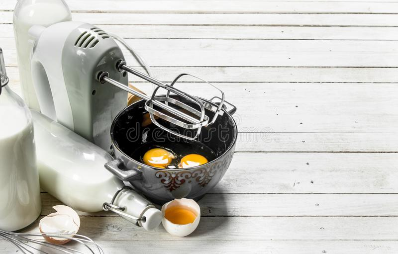 Fondo de la hornada Huevos frescos con un mezclador foto de archivo