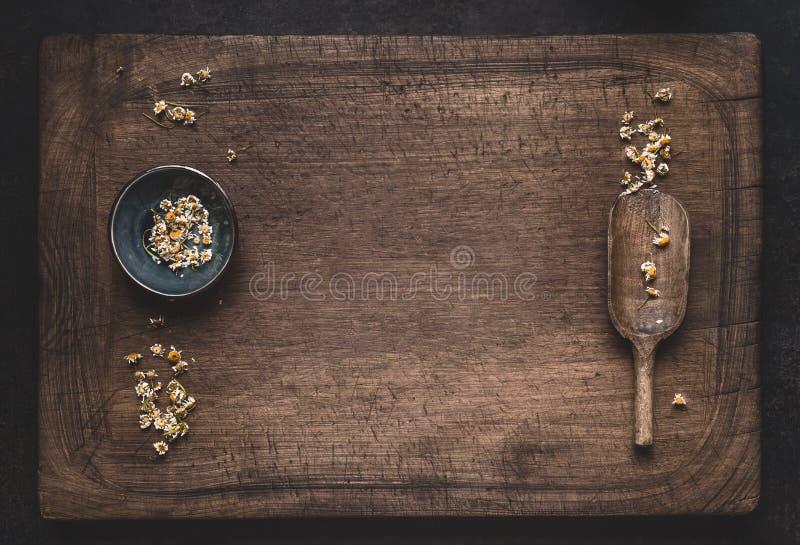 Fondo de la medicina herbaria con las flores secadas flojas de la manzanilla en cuenco con la cuchara en la visión de madera, sup fotografía de archivo