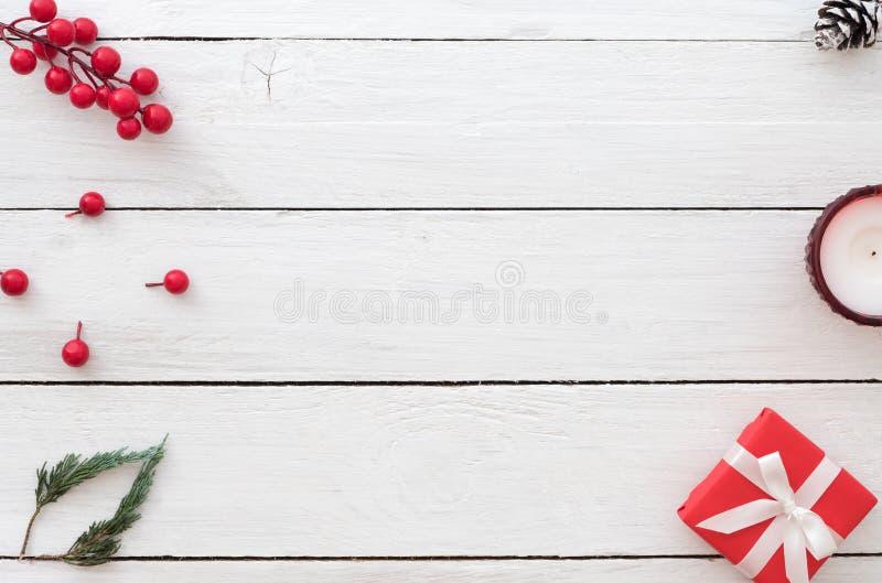 Fondo de la Navidad con la caja de regalo, la baya del acebo, las hojas del abeto, el cono del pino y la vela rojos en el fondo d imagen de archivo