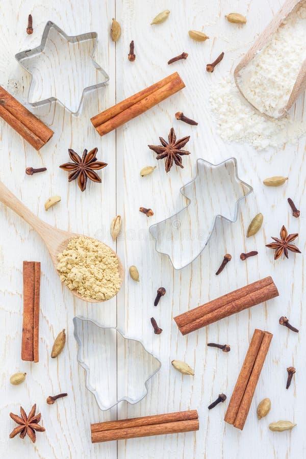 Fondo de la Navidad con diversos cortadores de las especias, de la harina y de la galleta en la tabla de madera blanca, vertical foto de archivo