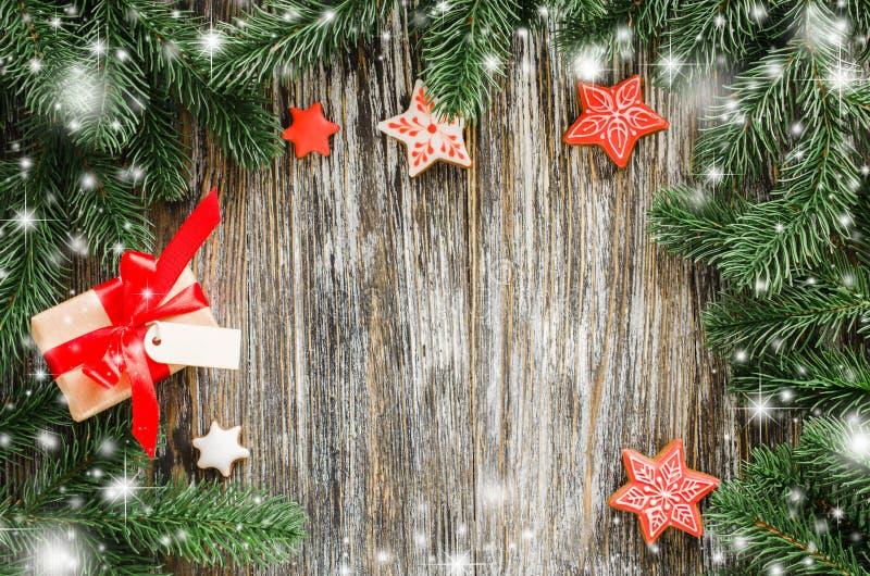 Fondo de la Navidad con el árbol de abeto, el pan de jengibre y el regalo imagen de archivo