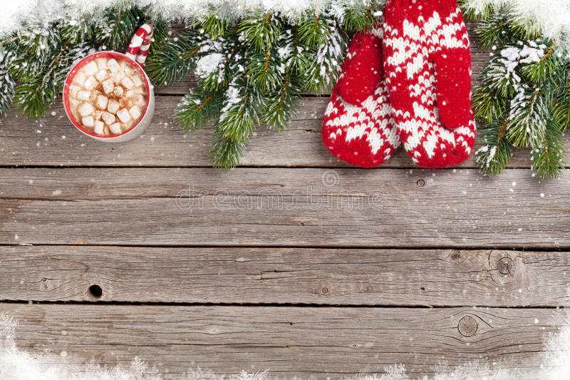 Fondo de la Navidad con el árbol de abeto, manoplas, chocolate caliente imagen de archivo