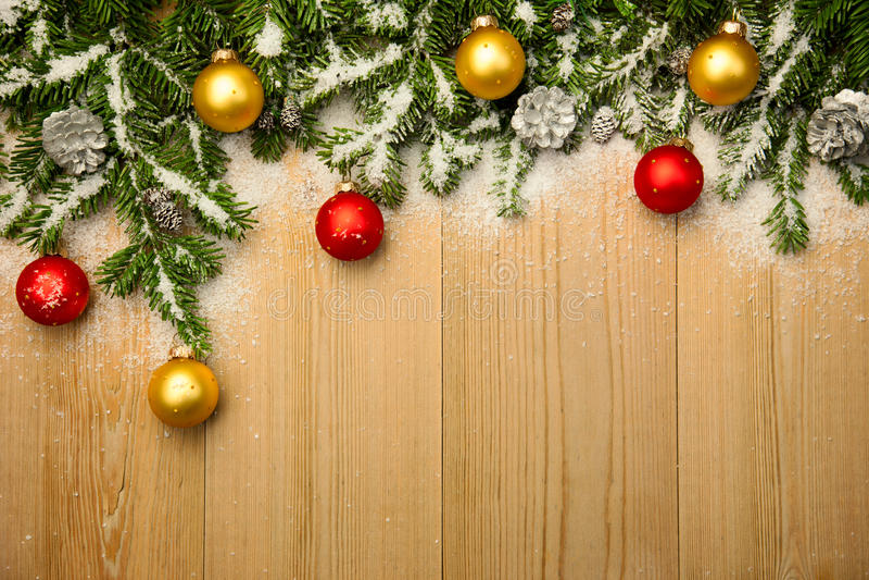 Fondo de la Navidad con el abeto y las chucherías en la madera con nieve fotos de archivo