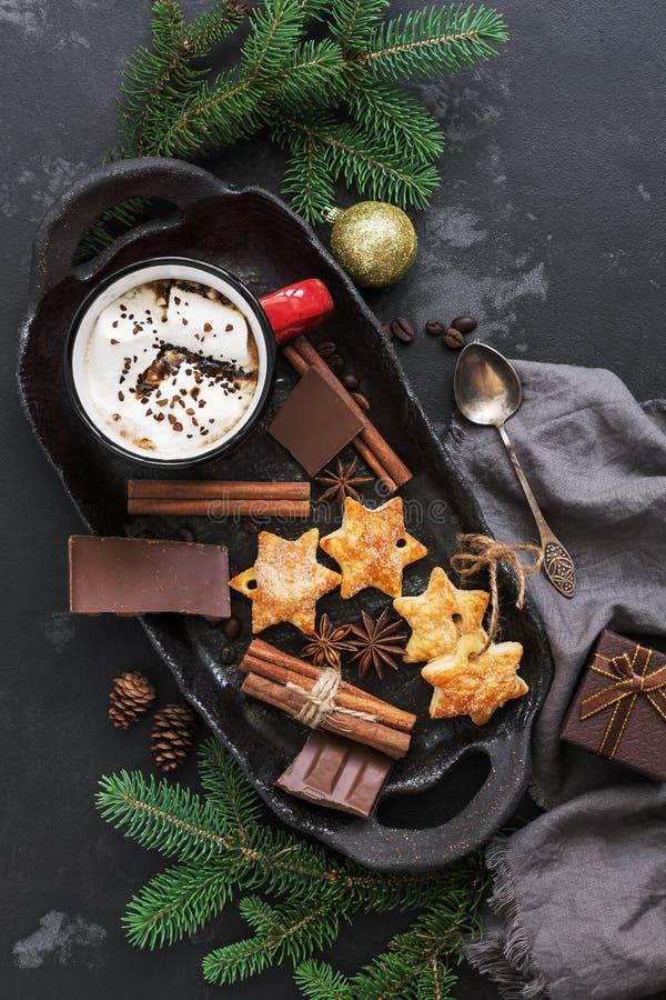 Fondo de la Navidad con el chocolate caliente en una taza roja con las melcochas, las galletas, las especias y el chocolate en un foto de archivo
