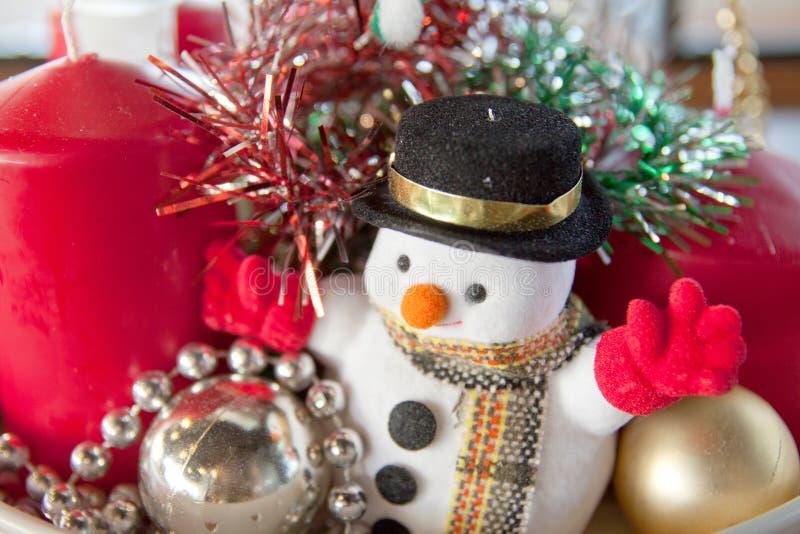 Fondo de la Navidad con el muñeco de nieve y los ornamentos de la Navidad con la decoración de la vela imagen de archivo libre de regalías