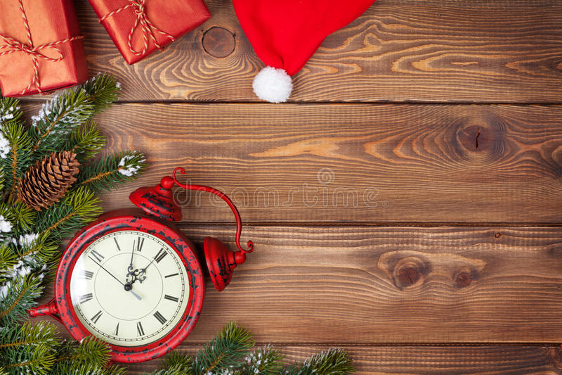 Fondo de la Navidad con el reloj, el árbol de abeto de la nieve y las cajas de regalo imagen de archivo
