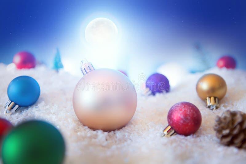 Fondo de la Navidad con las bolas de la Navidad en nieve sobre abeto, el cielo nocturno y la luna Profundidad del campo baja imagenes de archivo