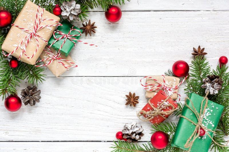 Fondo de la Navidad con las decoraciones, los conos del pino y las cajas de regalo cubiertos con nieve foto de archivo