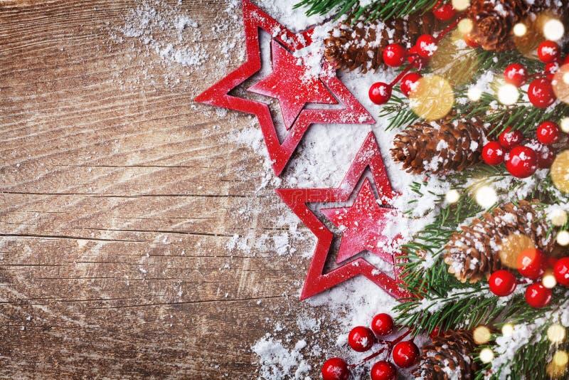 Fondo de la Navidad con las estrellas, las ramas nevosas del abeto, los conos y las luces del bokeh Bandera del día de fiesta fotografía de archivo