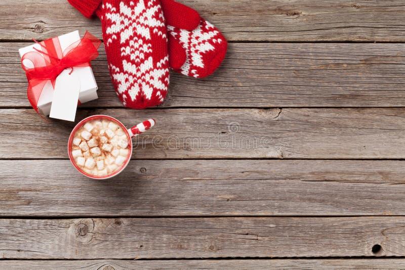 Fondo de la Navidad con las manoplas, el regalo y el chocolate caliente fotos de archivo