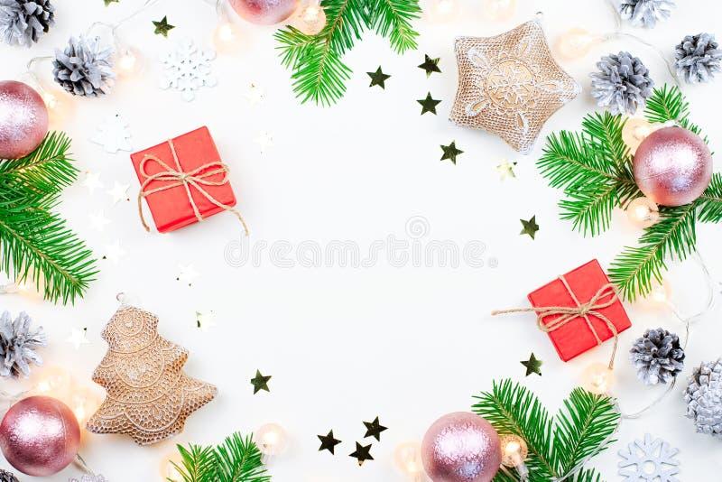 Fondo de la Navidad con las ramas de árbol de abeto, giftboxes rojos, luces de la Navidad, decoraciones rosadas, ornamentos de pl imagen de archivo